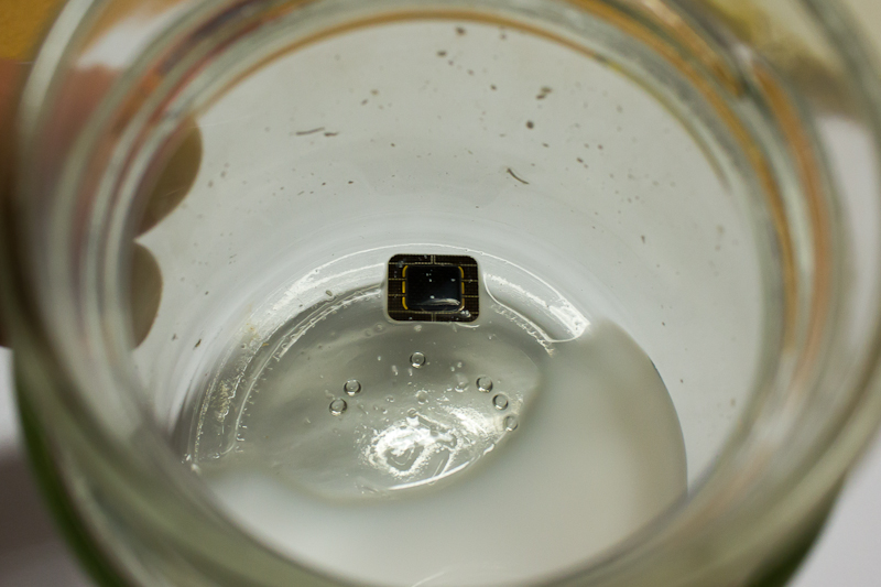 A SIM card being rinsed in acetone. The plastic has completely dissolved.
